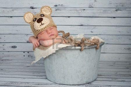 Vijf dagen oude pasgeboren baby jongetje draagt een bruine gehaakte Teddybeer hoed en slapen in een gegalvaniseerde emmer Shot in de s...