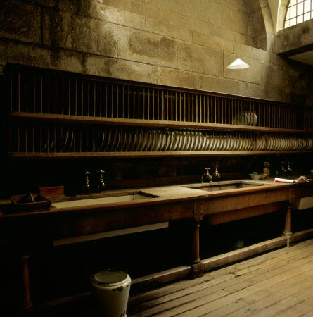 Three large oak-framed sinks and the long rows of plate racks above partially lit in the Scullery at Castle Drogo, Devon.