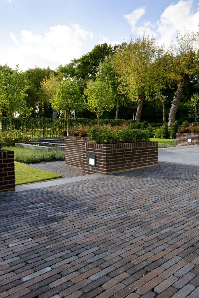 Verhoogd terras van gebakken klinkers met mooi uitzicht op open en strakke tuin