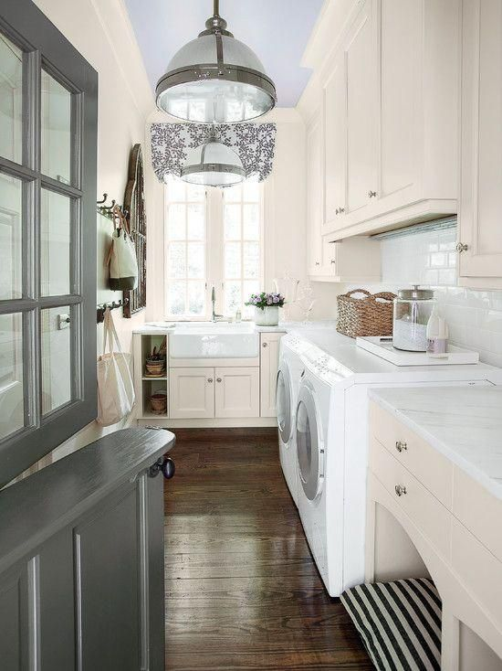 Laundry rooms don't have to be a hidden room that no one can see. Instead, it should be a room you are proud to display. We love the elegant, yet functional design of this laundry room. Even though the folding table doubles as a dog bed, the marble countertop adds a touch of glam. The apron-front sink is a functional yet great design choice and the modern lighting fixtures work since they play off the hardware choices.