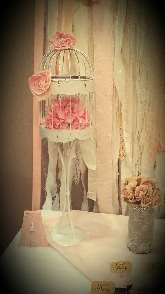 "Shabby chic vintage baby shower decor..bought cheap bird cage and old metal candle stand..spray painted white..dinged up for shabby look..added paper flowers with shiny glitter accents and pearls in centers. The ""A"" is shabby pink painted with lace overlay and small fabric flower added"