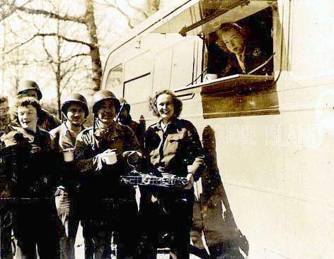 Janet Blair (holding donuts) of the American Red Cross is serving refreshments to the boys of Normandy from an ARC Clubmobile, France, 1944.