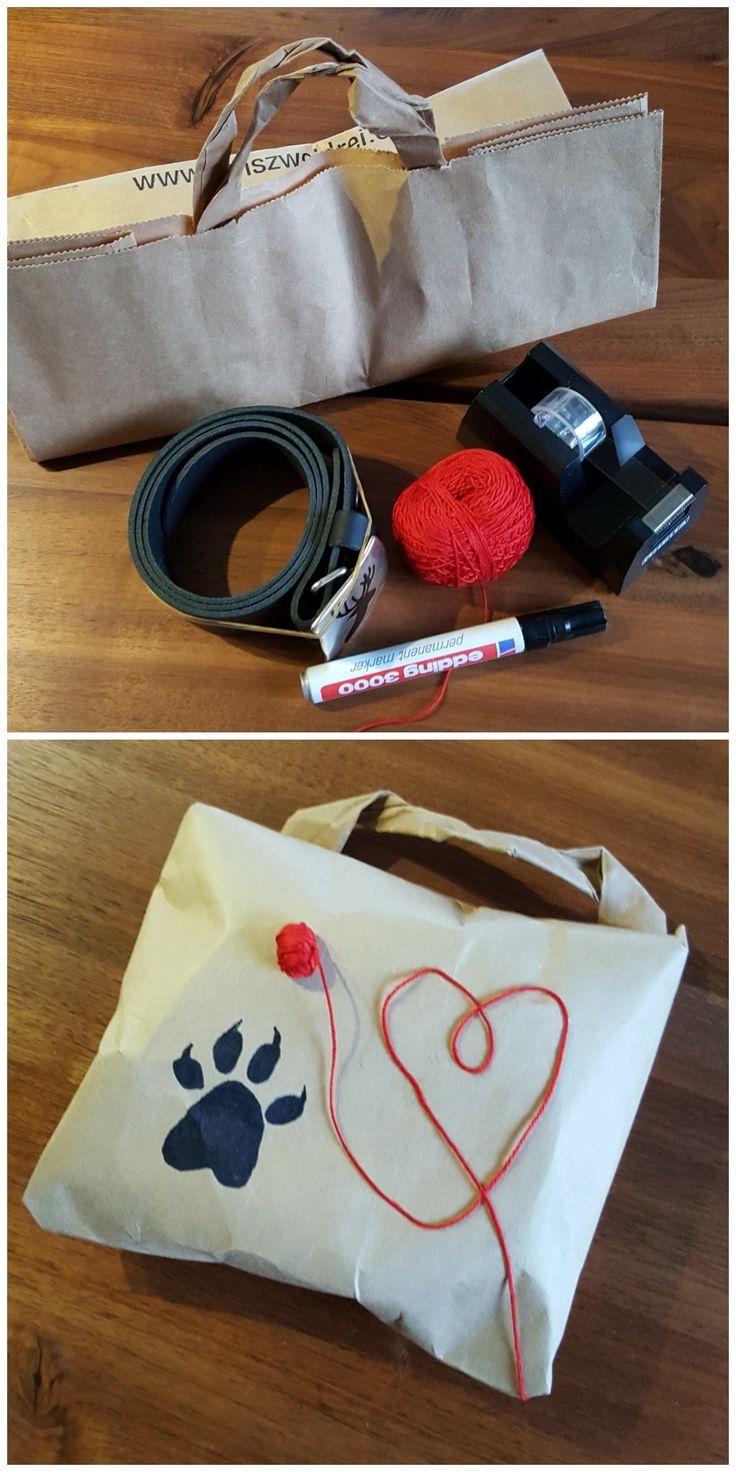 """Looks like the paw of Jack Wolfskin 😊.  Hier verpacke ich einen Gürtel für meine Nichte. Eine  Papiertragetüte entsprechend geschnitten, li. Seite genommen. Den einen Griff habe ich mit eingearbeitet. Aus Stickgarn ein Knäul gemacht  mit """"Herzauslauf"""". Mit schwarzem Edding eine Hundepfote (sie steht auf Hunde) gemalt. Das kann jeder. Man braucht nichts zu kaufen. 🤗"""