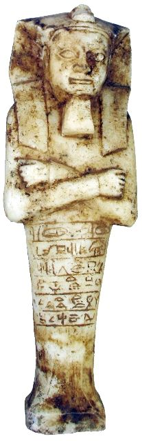 "Carved solid marble Ushabti, arms crossed, with chin beard and large headdress, an animal on the top. Six lines of hieroglyphs on the front.  26th Dynasty. 663-525 BC (11 ¼"" x 4"")    Often called ""Servants of the Afterlife"", Ushabtis were placed in the tomb of the mummy and were intended to be servants that would magically come to life and do any chore the mummy might be called upon to perform in the afterlife."