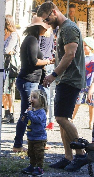 Doting dad: The 32-year-old affectionately leaned down, flaunting his extremely muscular a...