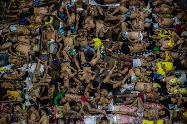 Des détenus dorment les uns sur les autres sur le terrain de basket de la prison surpeuplée de Quezon City, à Manille, le 19 juillet 2016 / AFP