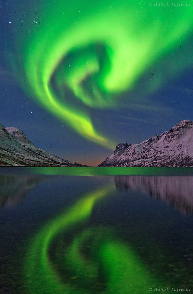 The northern lights or aurora borealis swirls over a fjord in the Norwegian Sea near Tromso, northern Norway.