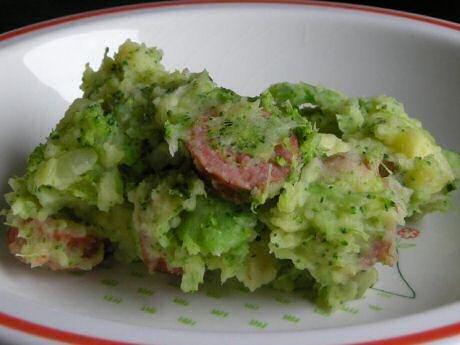 Een bord broccolipuree met stukjes aardappel, ui en worst