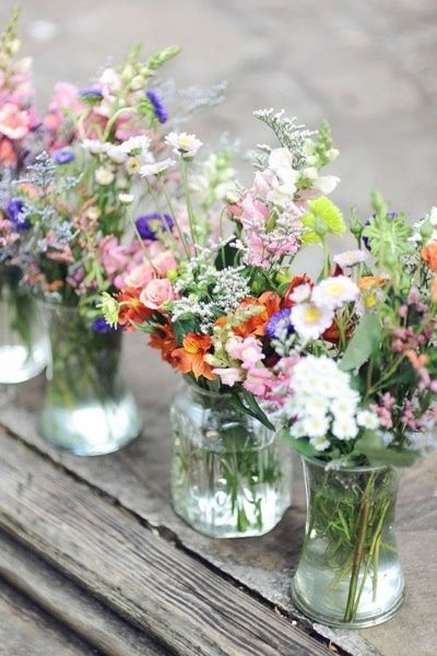 when working with a tight budget wild flowers in different size jars give a beautiful english country garden look