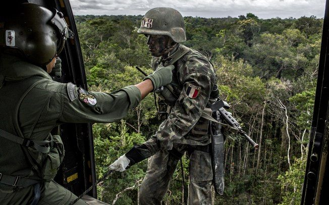 Instrutor militar brasileiro ajuda a oficial do exército francês, à direito, em rapel de um helicóptero durante o curso. Foto: Mauricio Lima /The New York Times
