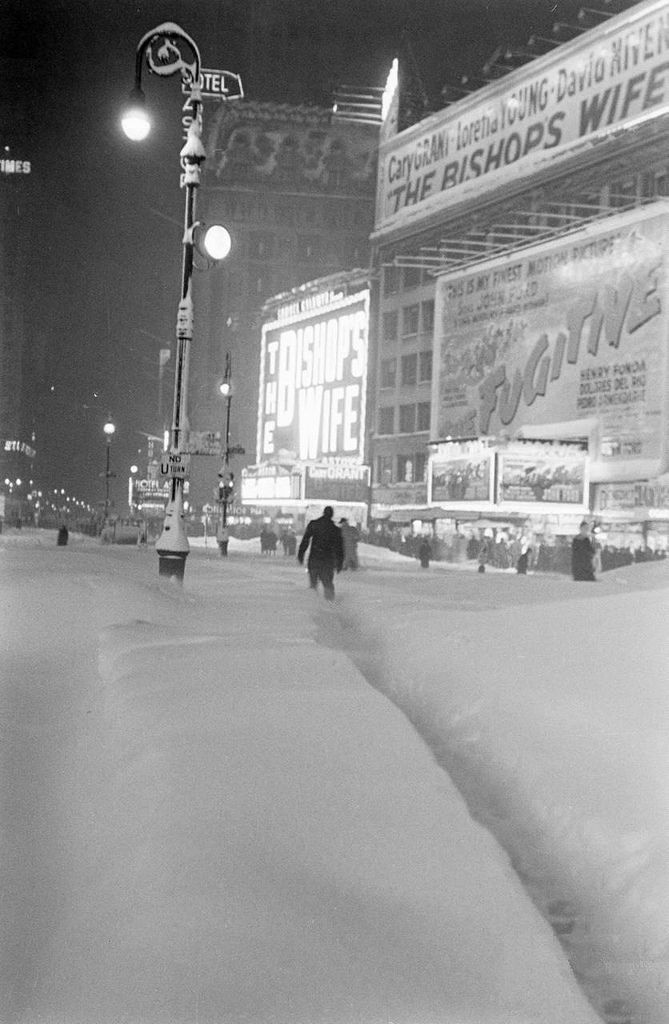 """NYC. Cold night at Times Square during 1947 blizzard. """"The Bishop's Wife"""" and """"The Fugitive"""" on the billboards invite to enter the movies"""