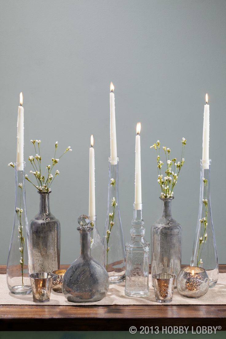 Brighten up an entryway table with large glass vases displaying candles and greenery.