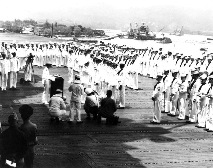 Admiral Chester W. Nimitz presents awards on the flight deck of the carrier Enterprise (CV-6) moored at Pearl Harbor on 5/27/1942. Note the battleship Oklahoma (BB-37) (capsized, nearest to camera) & West Virginia (BB-48) & Arizona (BB-39) behind her. One of those visible receiving a medal is Dorie Miller, an African-American messman who was awarded the Navy Cross for his heroic actions on board the battleship West Virginia (BB-48) during the Pearl Harbor attack.