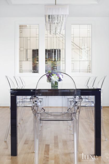 Louis and Victoria Ghost chairs from Design Within Reach surround a deep violet Coda table from Roche Bobois in the dining room. A Dainolite chrome chandelier, from The Lighting Outlet New York, suspends above.