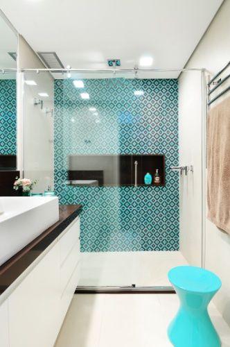 """O banheiro da suíte do apê Jardim Marajoara foi revestido por azulejos turquesa (20 cm X 20 cm) da Portobello e porcelanato """"off-white"""" Colorless, da mesma marca. Para finalizar, toques de marrom no nicho do boxe e na pia, em granito. O projeto de interiores foi assinado pela arquiteta Ana Yoshida"""