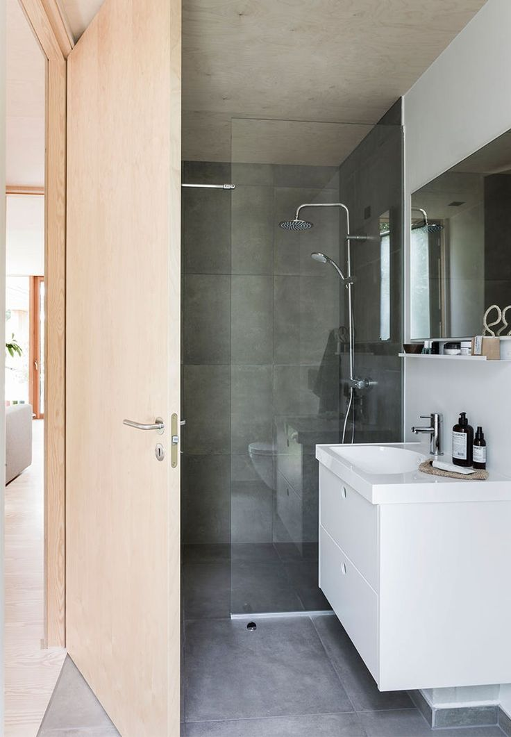 Minimalistic and simple bathroom with elements from Ikea and luminaire from Vola.