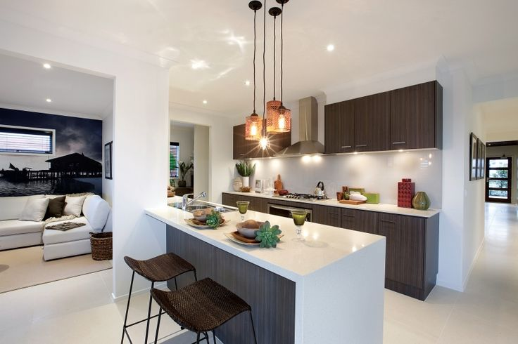 Amber pendant lighting and dark chocolate cabinetry give this kitchen a resort style feel. White benchtops bring the freshness and rattan furniture brings the relaxation.