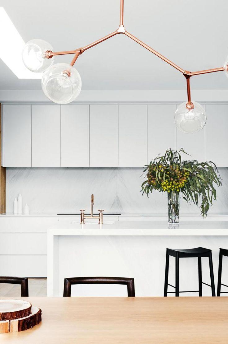 White handleless kitchen cabinets, marble splashback, copper tapware, metallic copper branch pendant light, black bar stools