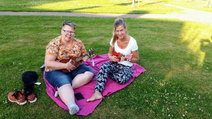 Två av deltagarna i Ukulelegruppen sitter och spelar i solen.