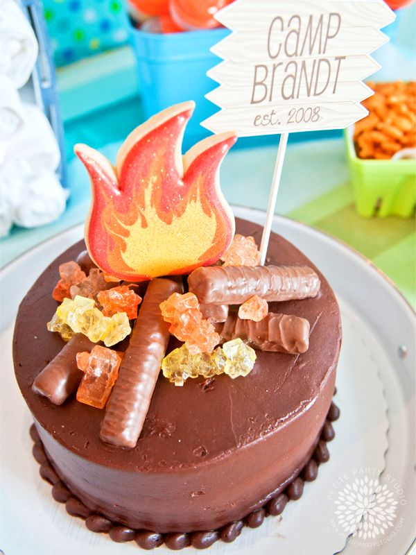Campfire Birthday Cake:a 2 layer simple cake made with added some twix candy bars for firewood, rock candy crystals for embers and enlisted cookie genius Casey's Confections to create the flame cookie.