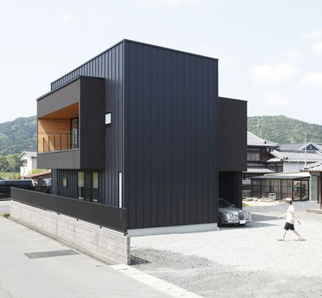 A cantilevered box containing a wood-lined terrace extends from the vertical core of this house in the Japanese prefecture of Shiga