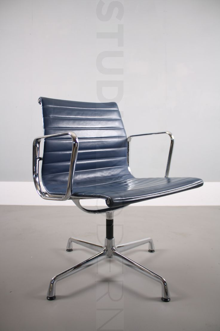 Vitra Charles & Ray Eames EA108  The frame is chromed aluminum and the upholstery is dark blue leather Condition: 7/10 This chair has some wear to corners. Please see photos