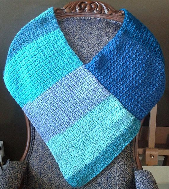 Triangular crochet short poncho in greens and blues