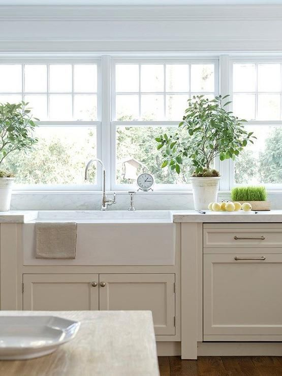 Exquisite kitchen features tan cabinets paired with white marble countertops fitted with a wide apron sink and gooseneck faucet placed below a bank of windows.