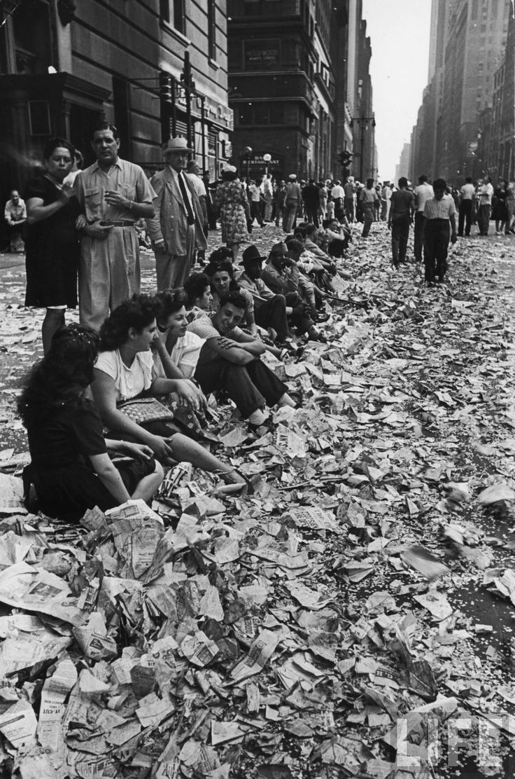 People sit on the curb amongst the confetti, ticker-tape and paper from the parade celebrating the end of WWII in NYC on VJ Day. August 14, 1945.