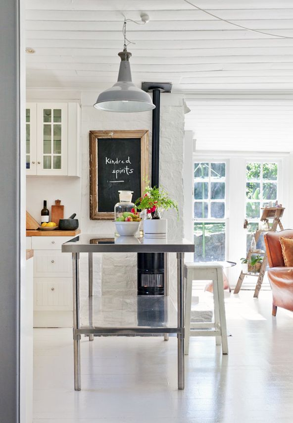 White kitchen with a stainless steel work table as an island & barn lamp. Love.