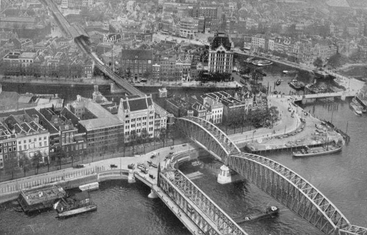 """De Scheepsmakershaven en het Witte Huis de Oude Haven. Onder in beeld de oude Willemsbrug en de spoorbrug. Deze brug is, samen met het hele """"luchtspoor"""" begin jaren vervangen door een tunnel. Na de brug over de Wijnhaven zien we de korte overkapping van station Beurs, later Blaak genoemd. Bij de aanleg van het ondergrondse Blaak station zijn resten van een oude stadsmuur gevonden. Deze zijn later op EXACT de zelfde plaats weer opgebouwd, hangend boven het perron."""