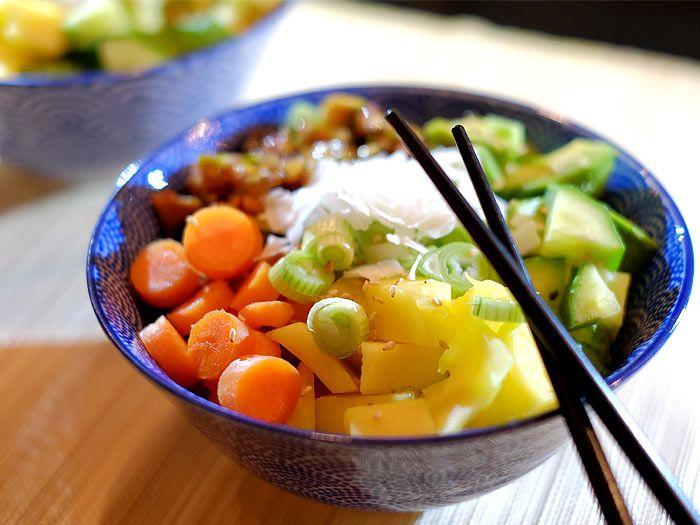 Poké bowl met gegrilde kip, avocado, mango en wortel