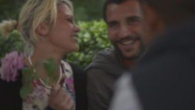 Young beautiful woman at italian restaurant kiss on the cheek a young beautiful man after he present her a rose in summer day ebening - HD video footage - HD stock video clip