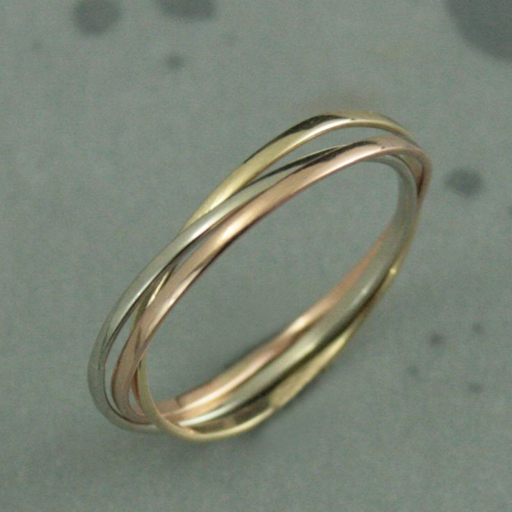 Now our popular rolling rings are available in solid 10K gold! Each band in this petite interlocking set measures 1mm wide by .5mm thick--petite enough that you will hardly know you are wearing them. Your ring will be handmade in three colors of solid 10K gold--white, yellow and rose. It will be made to size and be either high polished or given a soft brushed finish.  Please dont hesitate to contact us with any questions or concerns. All of our jewelry is hand made by either myself or my…