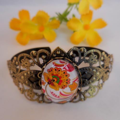 Armband die Victoriaanse glamour uitstraalt. Centraal staat een Oosterse pentekening, gezet achter een beschermend glaasje.  Bronskleurige armband, afgewerkt met bloemen en fijn filigraan.