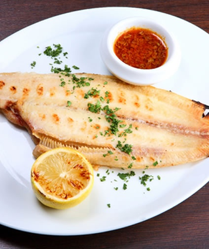 Whether you have some authentic sole (Dover sole) or a fish labeled as sole (probably flounder), both are delicious fish varieties and there are many different ways of preparing sole recipes. The following recipe uses lemon, mustard, and parsley for an elegant and classic flavor. The fish marinates in the lemon juice and balsamic vinegar mixture, to infuse it with flavor, and this sole recipe is delicious, especially served on a bed of fluffy white rice.