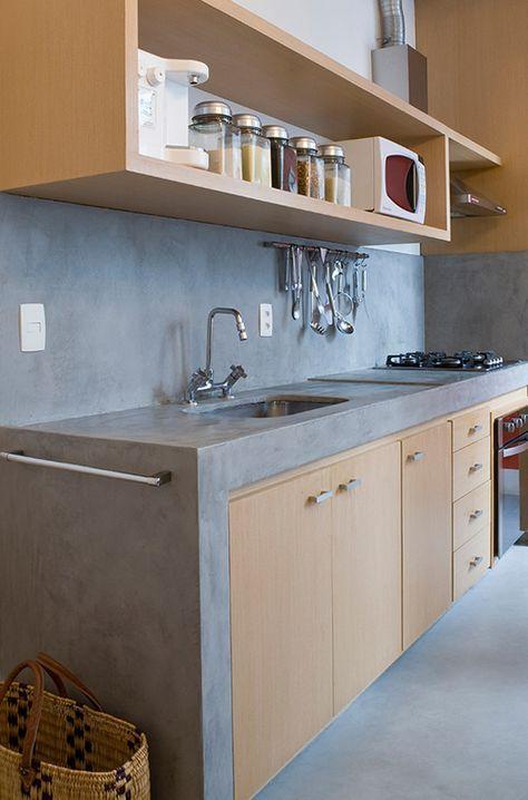 Cozinha com bancada de alvenaria e piso de cimento. Apartamento reformado com baixo custo usando móveis de alvenaria e iluminação exposta sem rebaixamento em gesso.