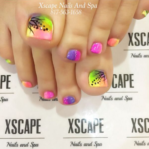 Gradient themed toenail art design. Make use of pleasant looking colors such as pink, violet, yellow and green to form the gradient effect. On top of the gradient you can add little details such as polka dots and curves with black polish.