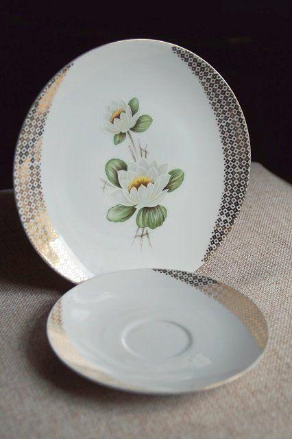 Dwa talerzyki porcelanowe, ze złotym wzorem na brzegach. Jeden mniejszy: średnica 15 cm, drugi większy: średnica 20 cm. Większy talerz z lilią wodną. Sygnowane BAVARIA.