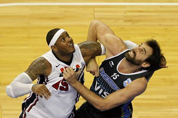 Carmelo Anthony (L) of Team USA fights for a ball against Federico Kammerichs of Team Argentina during their men's exhibition basketball game ahead of the London 2012 Olympic Games at Palau Sant Jordi arena, in Barcelona July 22, 2012. Yacare!