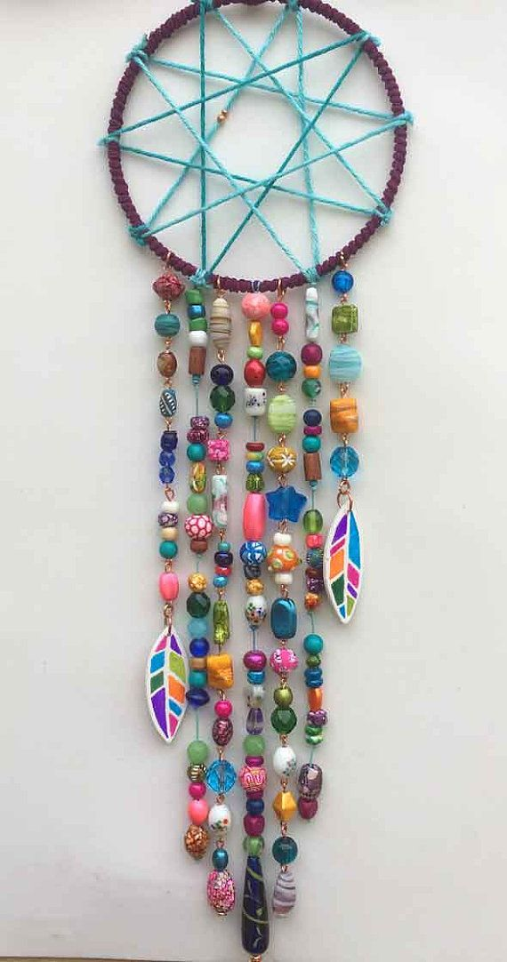 This is my version of a traditional dreamcatcher* I made it with lots of colorful beads and hand painted wooden feathers. It measures 19 long by 5 1/4 wide *A dreamcatcher is intended to protect the sleeping from negative dreams, while letting happy, positive dreams through. --I ship USPS Priority (2-3 day) to US