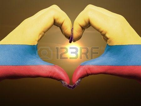 Manos con los colores de la bandera de Colombia, haciendo la figura de un corazón, al amanecer.   Gesto de las manos la bandera colombia colores que muestran el símbolo del corazón y el amor durante el amanecer Foto de archivo