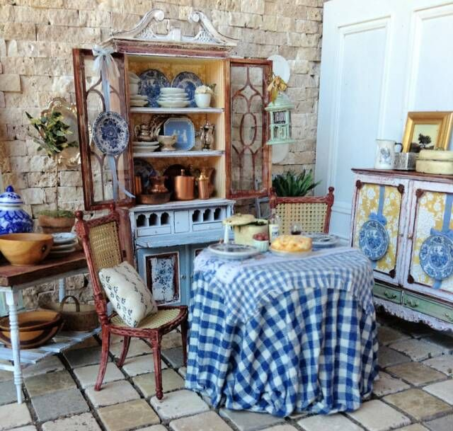 French country secretary, skirted table, woven cane chairs, and lots of blue and white accents. By Maritza Moran.