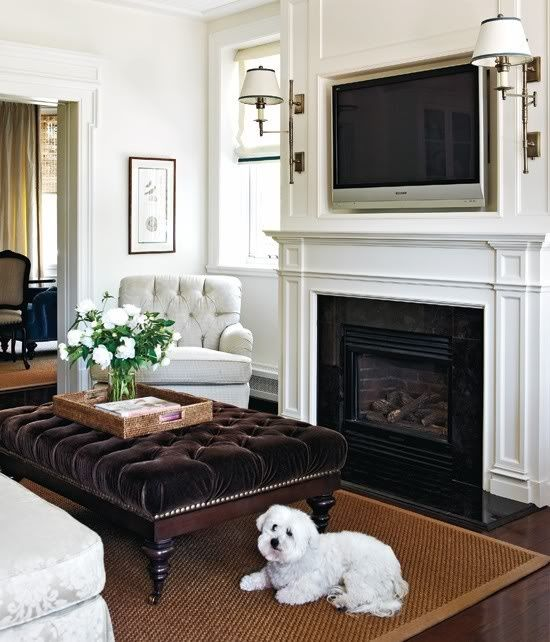 Traditional family room with windows covered in grosgrain roman shades flanking fireplace with ...
