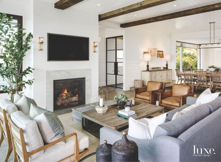 Interior designer Kari Arendsen chose reclaimed beams from Vintage Timberworks for the living area. Around an RH coffee table, Ralph Lauren Home armchairs, a sofa in Perennials fabric and Noir armchairs with cushions in a Schumacher linen make for stylish seating.
