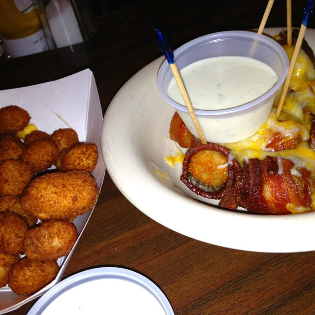Bacon wrapped tater tots with a slice of jalapeño smothered in pepper jack cheese. From the High Life Lounge in Des Moines, Iowa.