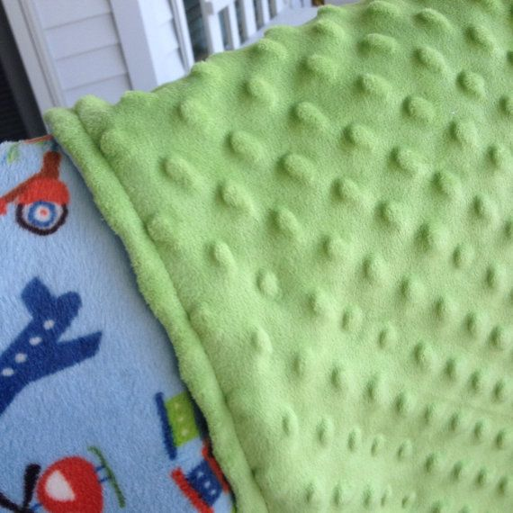 Tween/teen/toddler blanket with a transportation them on a blue background. The back is a sage green minky dot fabric. on Etsy, $47.00