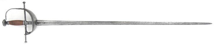 """R-C45B.- Espada de barquilla. España, primera mitad s.XVIII. Guarnición en hierro compuesta por una cruz de gavilanes rectos, escudetes, aro con calado formando un corazón invertido, pomo, dos virolas y cazoleta tipo barquilla con reborde decorado mediante canales y limados artísticos. Hoja recta, provista de vaceo en su primer cuarto, apreciándose inscripciones en ambos costados, de las cuales únicamente """"BRABENDER"""" es legible. Long. Total: 99 cms; Long.Hoja : 82,5 cms; Anchura base hoja…"""