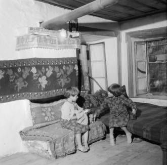 Greece, children playing with dolls inside home in Métsovon :: AGSL Digital Photo Archive - Europe