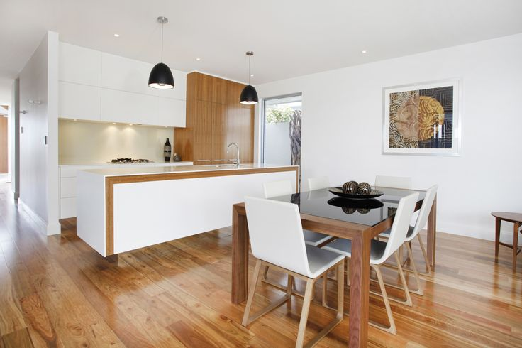 An all-white kitchen is brought to life with timber highlights which pick up the timber floor elements and connect with the adjacent casual dining space...